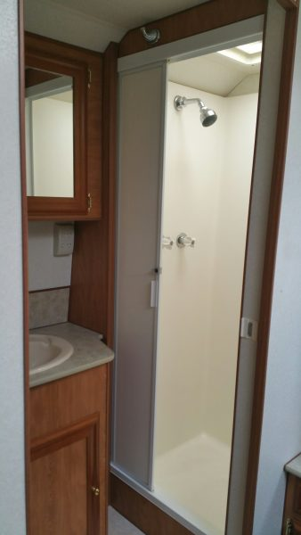 Shower and right of basin and cupboards